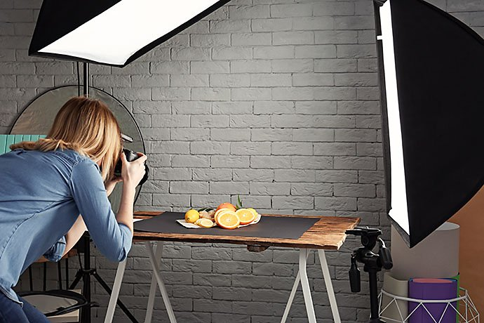 woman-taking-photo-of-food-with-professional-camera-in-studio