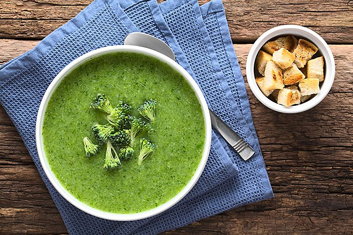 fresh-homemade-cream-of-broccoli-soup-in-bowl-garnished-with-broccoli-florets-fresh-crispy-croutons-on-the-side-photographed-overhead-selective-focus-focus-on-the-soup