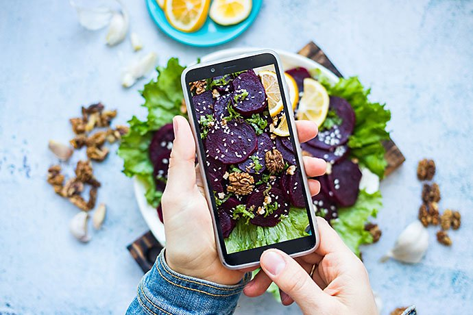 woman-take-picture-of-vegan-food-with-phone-at-her-kitchen-hand-make-a-closeup-smartphone-photo-of-beetroot-salad-with-walnuts-for-blogging-or-social-media-content-vegetarian-healthy-food