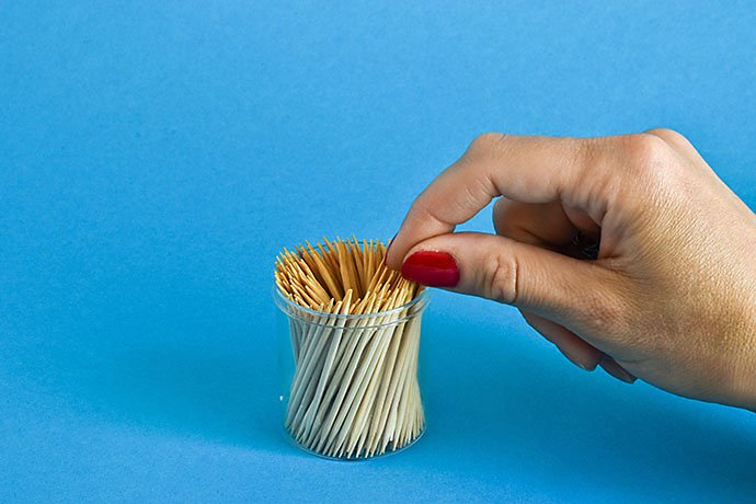 female-hand-takes-a-toothpick-from-a-can-on-a-blue-background-place-for-text