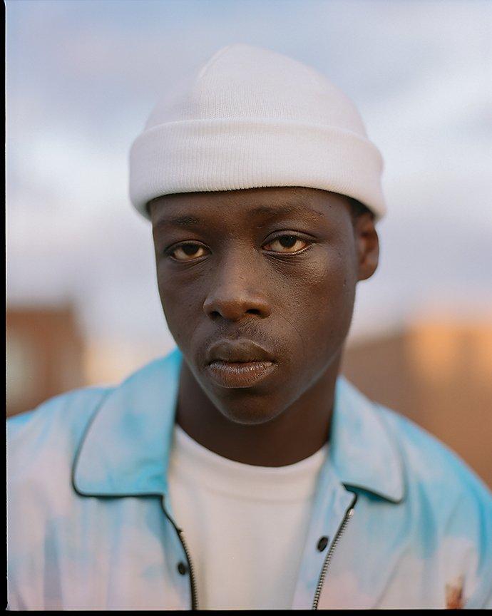 Man in white beanie hat captured in portrait photograph