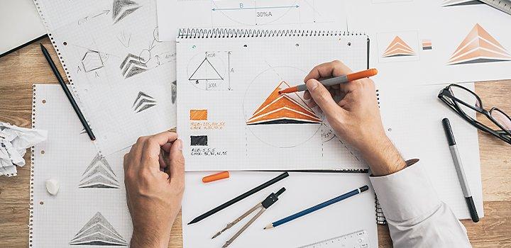 A person sketching various minimalist logo designs