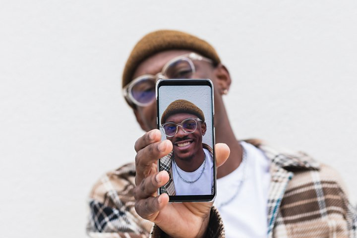 A person holding up their cell phone which has a selfie photo of themselves on the screen